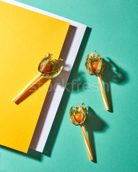 Flat lay view of the pattern of three yellow physalis fruit and plastic straws for juice with shadow Stock photo © artjazz