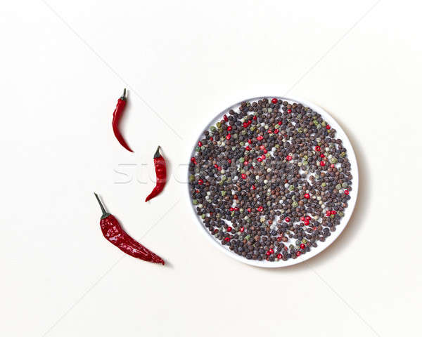 Red pipe pods of red chili peppers with mix of different kinds of pepper on a white plate on a white Stock photo © artjazz