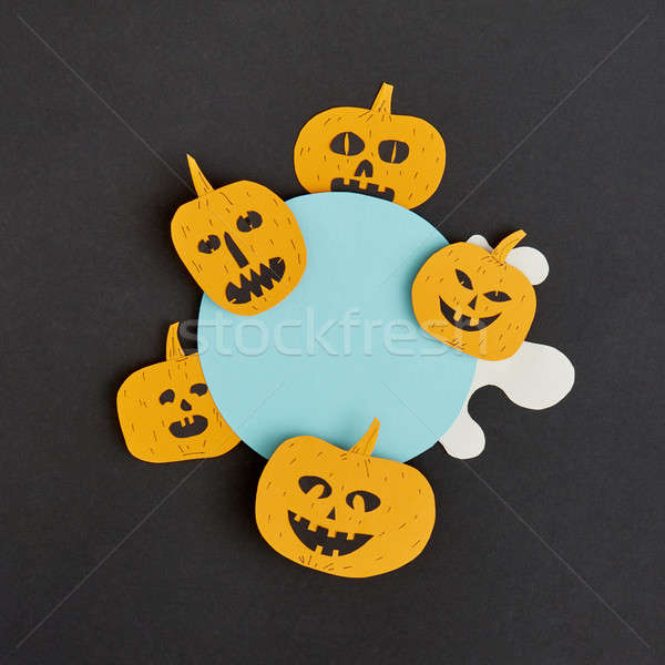 Stock photo: Creative Halloween handmade blue frame with paper horrible smiling and laughing pumpkins on a black