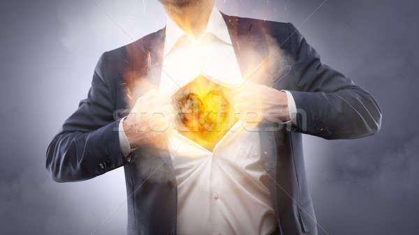 Businessman showing a burning heart Stock photo © artjazz