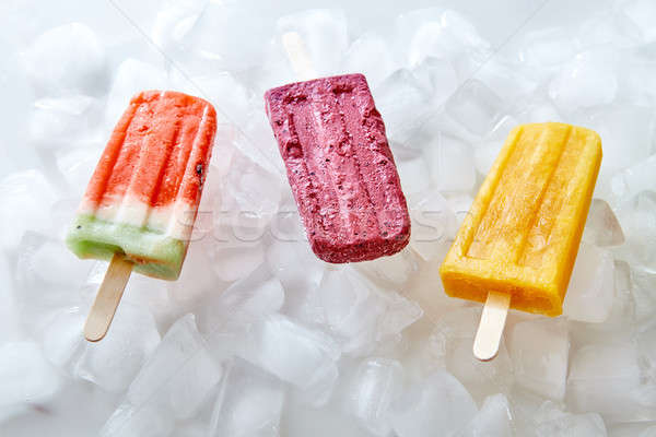 Watermelon, berry, peach, homemade ice lolly on ice cubes. Sweet cold dessert. Flat lay Stock photo © artjazz