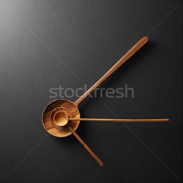 Top view of black alarm clock with wooden spoons Stock photo © artjazz