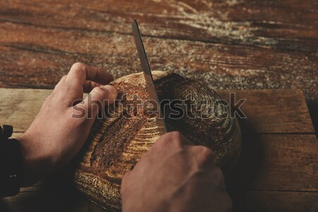 A man baker cuts bread Stock photo © artjazz