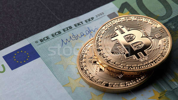 Two gold coins bitcoin stack on paper euro bill Stock photo © artjazz