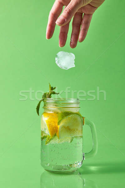 A girls' hand throws a piece of ice into a glass jar with a natural mojito cocktail. Stock photo © artjazz