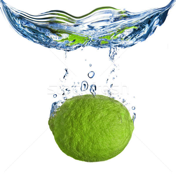 Fresh lime dropped into water with bubbles isolated on white Stock photo © artjazz