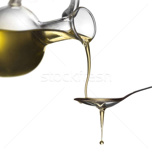 Stock photo: Pouring oil from jar on spoon isolated on white