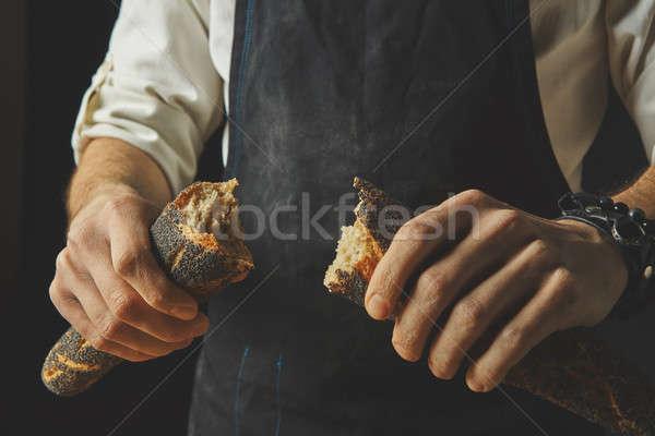 Hand breaks baguette Stock photo © artjazz