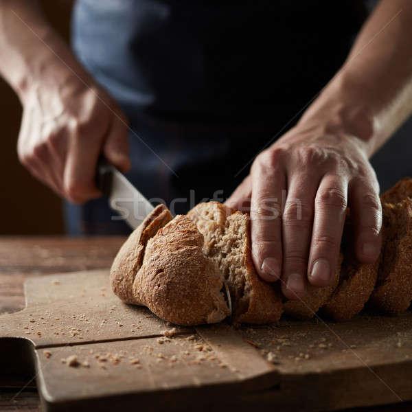 Male hands cutting wheaten bread, closeup Stock photo © artjazz