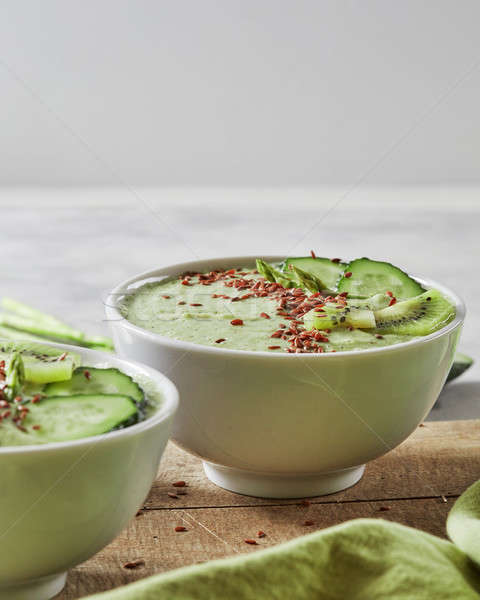 Stock photo: Green smoothies with a cucumber, kiwi and flax seeds in a plate on an old wooden board. Vegetarian f