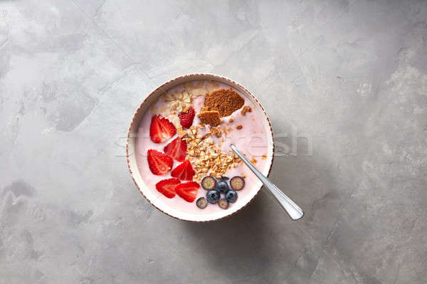 Top view of a plate with homemade granola,yogurt and berries on a gray concrete background Stock photo © artjazz