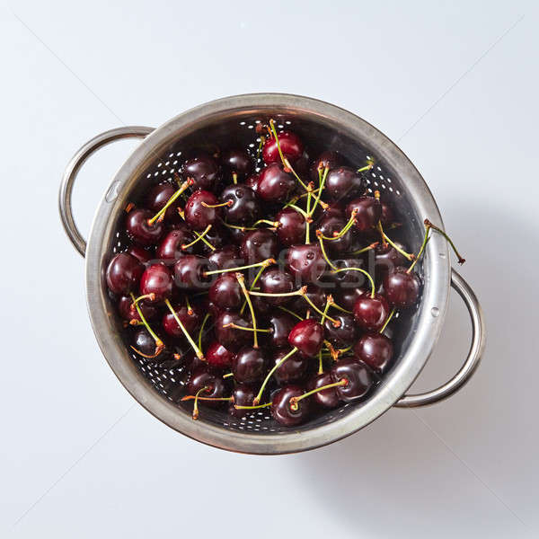 Red ripe sweet cherry berries with water droplets in a colander on a white paper background. Top vie Stock photo © artjazz