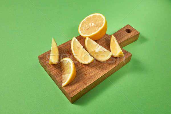 Half and slices of natural organic yellow lemon on a wooden brow Stock photo © artjazz
