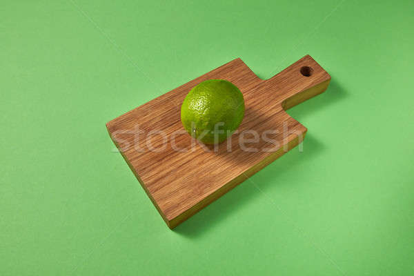 Whole green ripe fresh organic lime on a wooden brown board on green background. Top view. Stock photo © artjazz