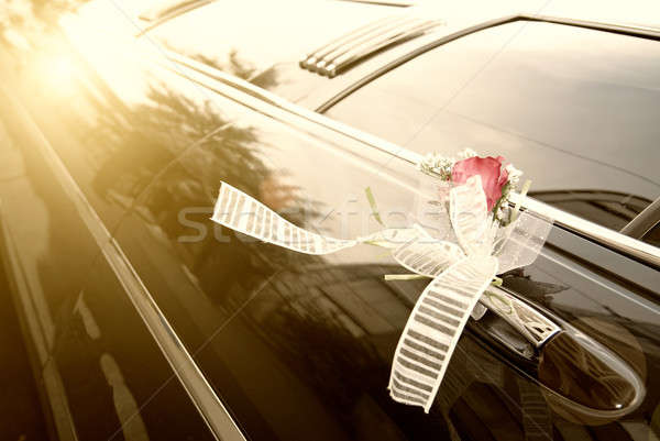 Stock photo:  Door of black wedding car with flower and  ribbon