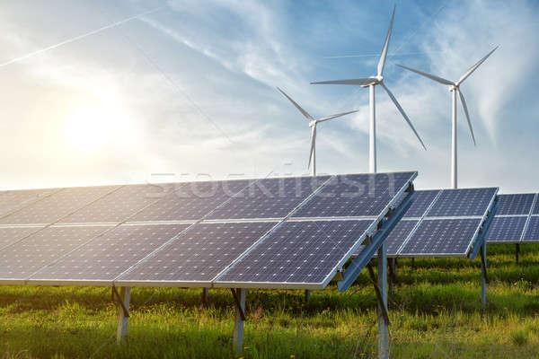 solar panels and wind generators under blue sky on sunset Stock photo © artjazz