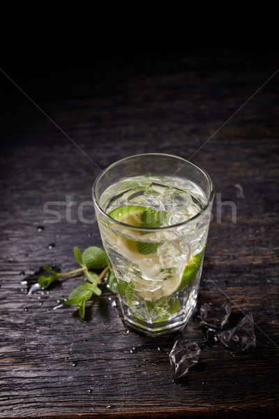 From above shot of mojito cocktail with ice and mint in glass on dark background Stock photo © artjazz