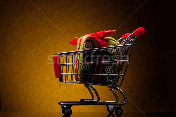 shopping cart with gift on yellow background Stock photo © artjazz