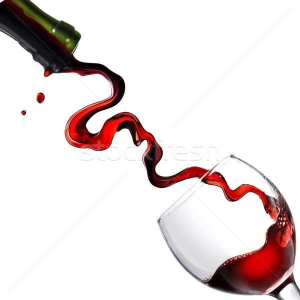 Pouring red wine in glass goblet isolated on white Stock photo © artjazz