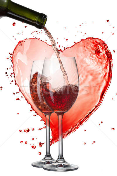 Red wine pouring into glasses with splash against heart isolated Stock photo © artjazz