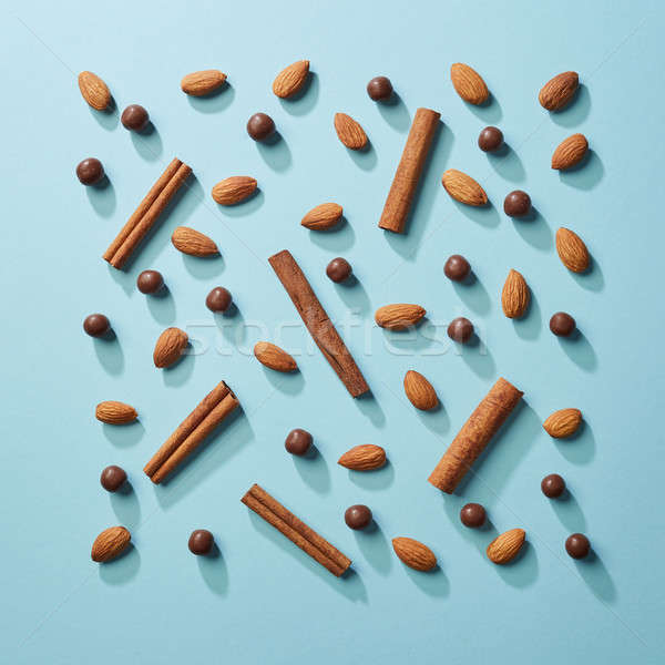 Pattern made of nuts, cinnamon and chocolate balls on a blue paper background. Flat lay Stock photo © artjazz