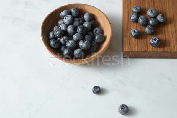 Summer organic natural sweet blueberries in a wooden plate on a white. Copy space. Stock photo © artjazz