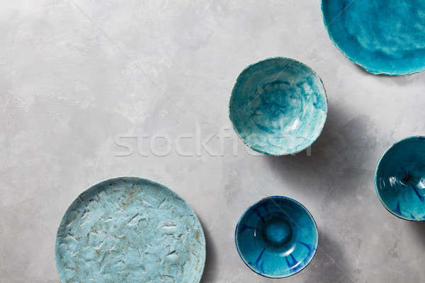 Porcelain blue bowls and plates on a gray marble table. Multi-colored ceramic vintage handmade dishe Stock photo © artjazz