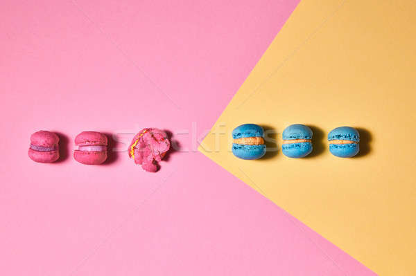 Stock photo: Row of different macaroons on a yellow pink background. Creative layout for your ideas. Flat lay