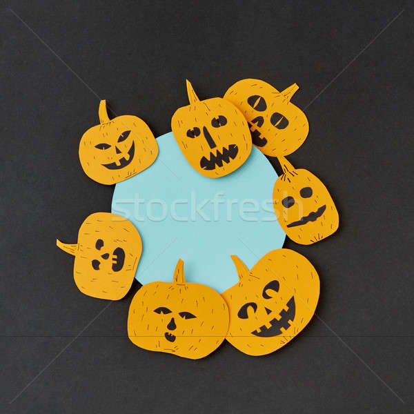 Decorative round blue Halloween frame handcraft with paper laughing pumpkin on a black paper backgro Stock photo © artjazz