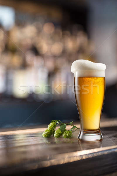 Glass of beer on wooden table and blurred background. Stock photo © artjazz