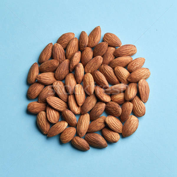 A circle of almonds on a blue paper background. Delicious healthy food Stock photo © artjazz