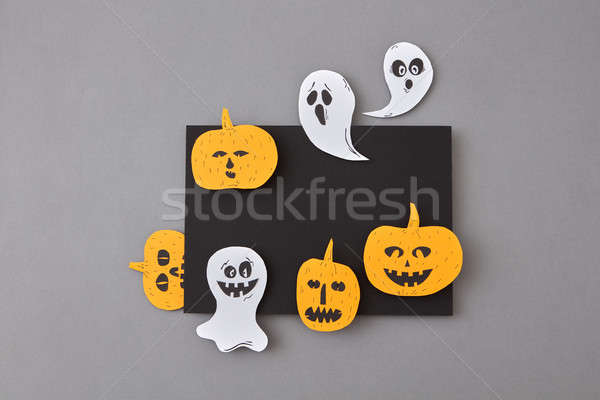 Black frame of flying ghosts, spirits and yellow scary pumpkins, handcraft from paper on a gray back Stock photo © artjazz