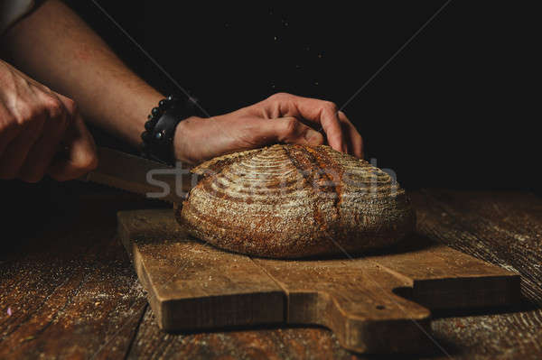 Hands of a young man cut fresh rye bread Stock photo © artjazz