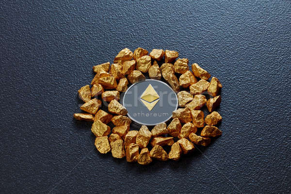 Etereum coin and golden nuggets on a black concrete background. Business, finance and technology con Stock photo © artjazz