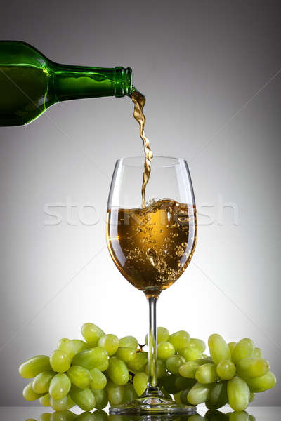 White wine pouring into glass from bottle with green grape Stock photo © artjazz