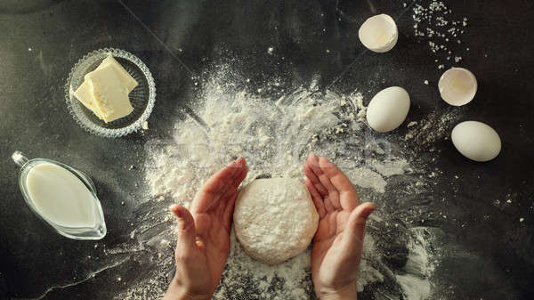 Woman's hands knead dough on table with flour Stock photo © artjazz