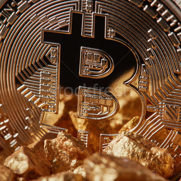 Closeup of golden Bitcoin Coin and mound of gold. Bitcoin cryptocurrency. Stock photo © artjazz