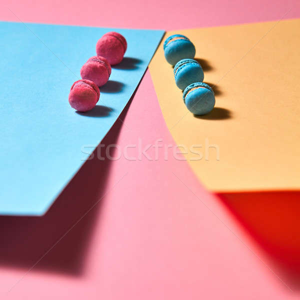Different macaroons presented in a row on a colored paper background Stock photo © artjazz