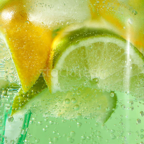 A natural fruit background with macro lime slices, lemon and a colored drinking plastic straw in a g Stock photo © artjazz