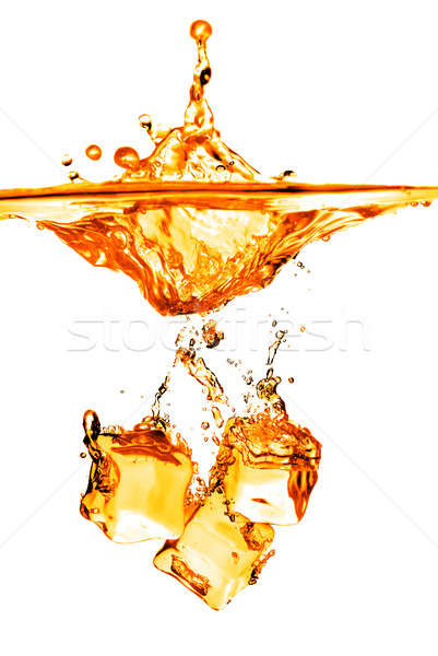 Stock photo: ice cubes dropped into orange water with splash isolated on whit