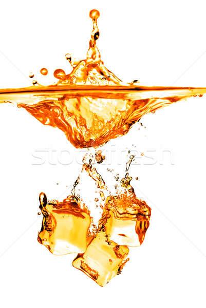 ice cubes dropped into orange water with splash isolated on whit Stock photo © artjazz