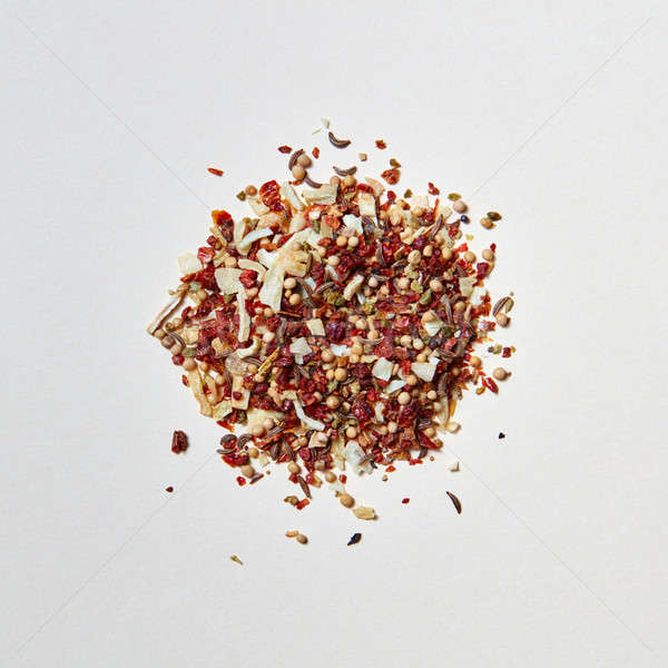 Colorful pattern of a mixed of fragrant natural spices for cooking meat on a white background. Stock photo © artjazz