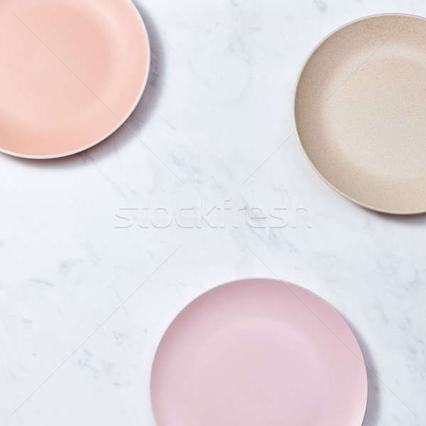 Traditional decorative ceramic handcraft plates covered with glazed on a gray background. Flat lay Stock photo © artjazz