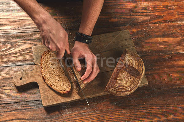 Men's hands cut fresh bread Stock photo © artjazz