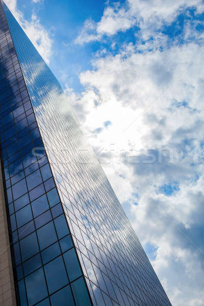 Modern smoked glass office building against a blue cloudy sky. Stock photo © artjazz