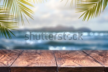 Stock photo: Empty wooden table and palm leafs on a background of beach blurred.