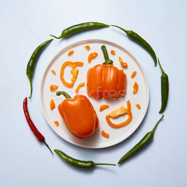 Plate with sliced colored peppers on a light background Stock photo © artjazz