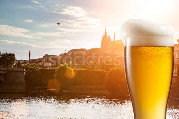 Glass of beer against view of the St. Vitus Cathedral in Prague Stock photo © artjazz