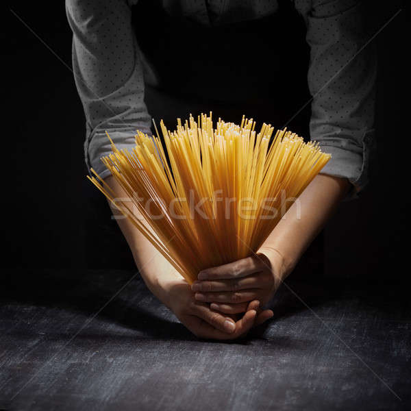 Woman's hands holding Raw spaghetti in dark background Stock photo © artjazz
