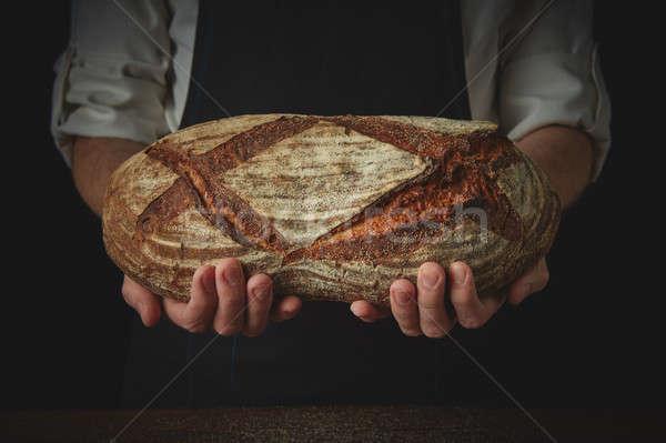Men's hands hold organic dark bread Stock photo © artjazz